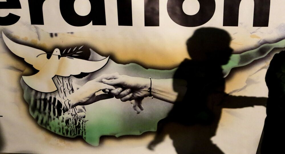 A shadow of a bo.y is seen on a banner showing the Cyprus island with two hands and a pigeon during a peace rally to support the peace talks inside the UN buffer zone Green Line, in the divided capital Nicosia in the eastern Mediterranean island of Cyprus.