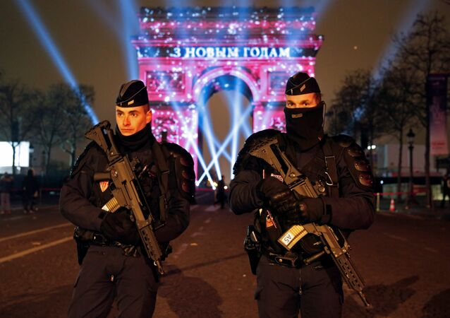 Policemen secure the Champs Elysees Avenue as Revellers gather during New Year celebrations in Paris,France, late December 31, 2016