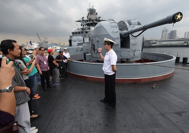 A Russian sailor (R) speaks to Filipino visitors during a public tour of the anti-submarine navy ship Admiral Tributs at the south pier in Manila on January 5, 2017