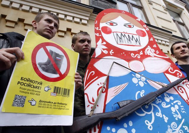 Protesters hold an angry Matryoshka with a weapon and placard reading Boycott Russia ! during an action in central Kiev, on April 9, 2014, calling for the boycott of Russian goods
