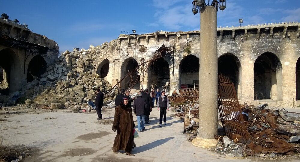Citizens at a yard of the Umayyad Mosque of Aleppo destroyed following military actions. The Umayyad Mosque was the largest and the oldest mosque of Aleppo