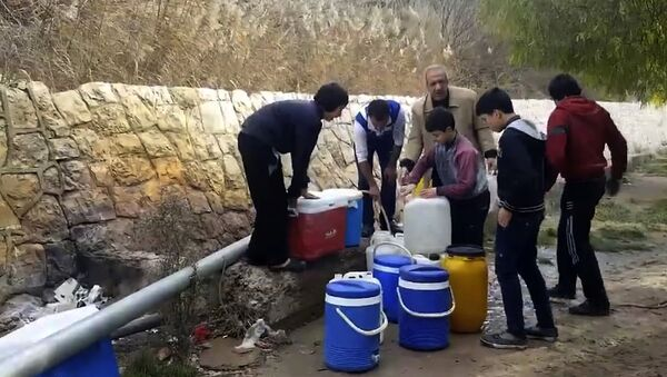 This frame grab from video provided By Yomyat Kzefeh Hawen Fi Dimashq (Diary of a Mortar Shell in Damascus), a Damascus-based media outlet that is consistent with independent AP reporting, shows Syrian residents filling up buckets and gallons of spring water from a pipe on the side of the road, in Damascus, Syria - Sputnik International