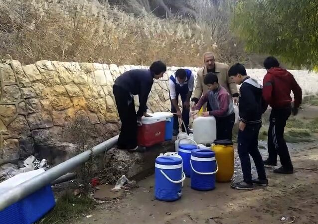 This frame grab from video provided By Yomyat Kzefeh Hawen Fi Dimashq (Diary of a Mortar Shell in Damascus), a Damascus-based media outlet that is consistent with independent AP reporting, shows Syrian residents filling up buckets and gallons of spring water from a pipe on the side of the road, in Damascus, Syria