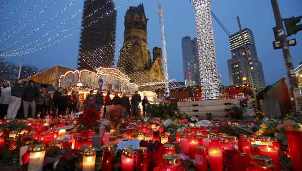Flowers and candles are placed near the Christmas market at Breitscheid square in Berlin, Germany, December 22, 2016, following an attack by a truck which ploughed through a crowd at the market on Monday night - Sputnik International