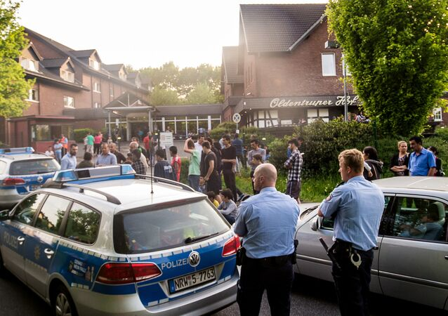 In this May 21, 2016 picture police and refugees stand near a refugee shelter in Bielefeld, Germany