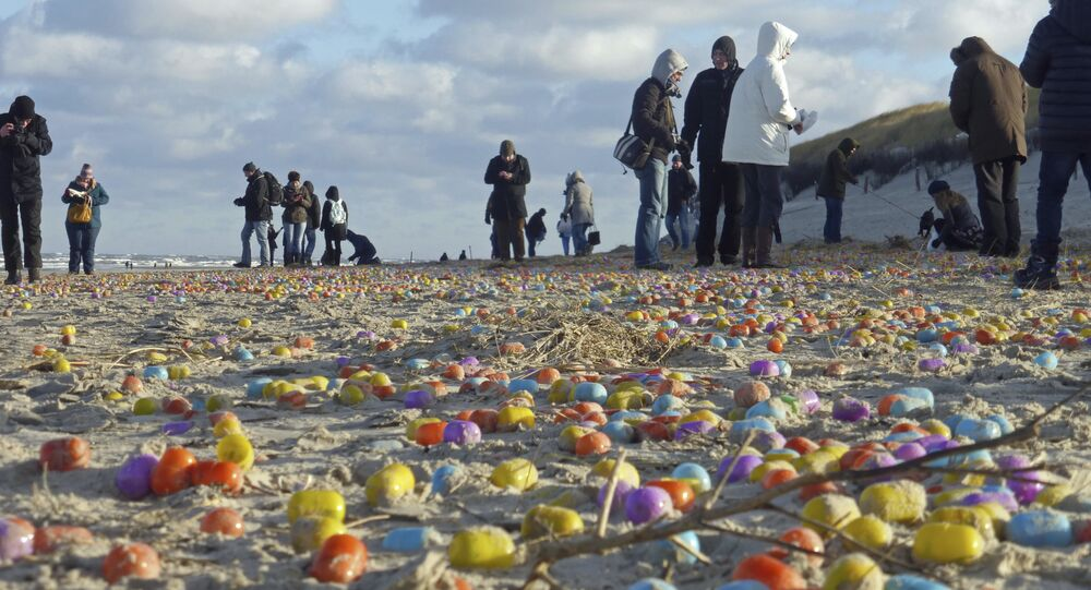 Tourists gather colorful plastic eggs on the beach of the German North Sea island of Langeoog, Thursday Jan. 5, 2017