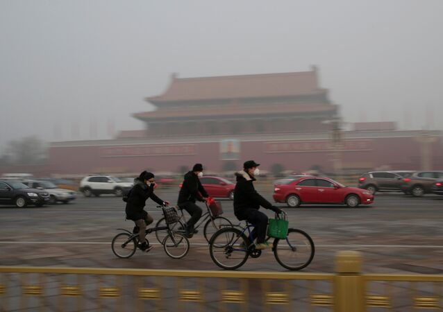 People wearing masks cycle past Tiananmen Gate during the smog after a red alert was issued for heavy air pollution in Beijing, China, December 20, 2016.