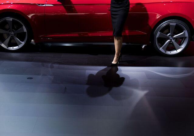 Модель позирует рядом с Audi S5 на автосалоне в Детройте
