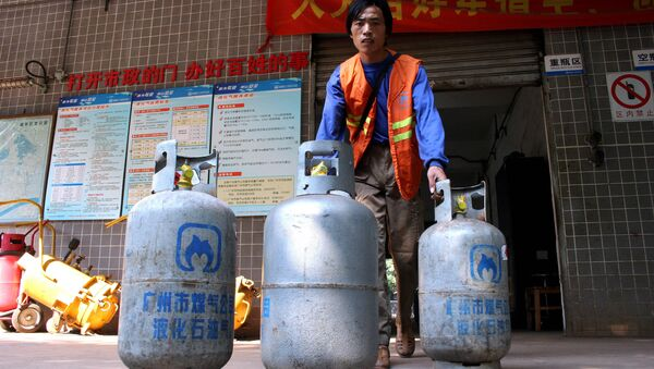 A worker delivers cylinders of liquefied petroleum gas (LPG) at a LPG service station in Guangzhou, southern China's Guangdong province. (File) - Sputnik International