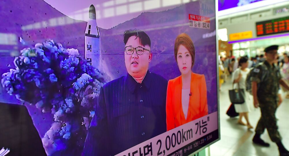 A South Korean soldier (R) walks past a television screen reporting news of North Korea's latest submarine-launched ballistic missile test at a railway station in Seoul on August 25, 2016