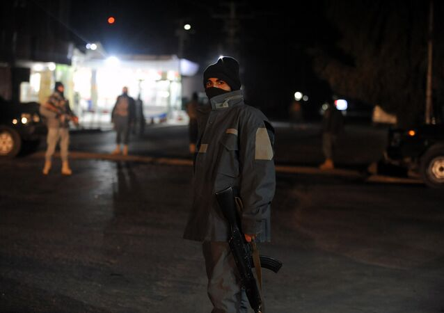 This picture taken on January 10, 2017 shows Afghan policemen standing guard at the site of an explosion near the governor's compound in Kandahar