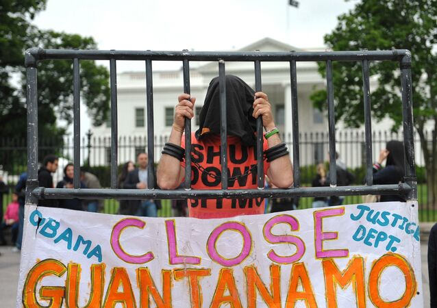 A hooded demonstrator is seen at a protest calling for the closure of the Guantanamo Bay detention facility in front of the White House on May 18, 2013 in Washington, DC.