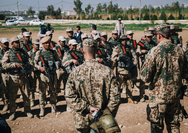 Kurdish Peshmerga soldiers listen to instructions by a German army trainer, at Bnaslawa Military Base in Irbil, northern Iraq, Wednesday, March 9, 2016