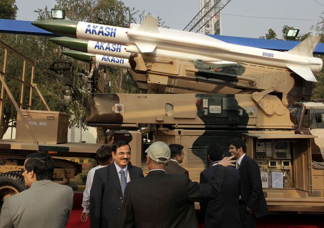 Visitors discuss in front of Defence Research & Development Organization's Akash medium range surface to air missile system, at the DefExpo-India 2010 , in New Delhi, India, Tuesday, Feb. 16, 2010