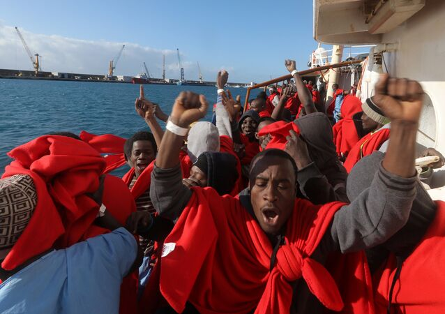 Migrants celebrate on board the former fishing trawler Golfo Azzurro as they arrive at the port of Pozzallo in Sicily, two days after they were rescued by the Spanish NGO Proactiva Open Arms after the raft they were on drifted out of control in the central Mediterranean Sea, January 4, 2017
