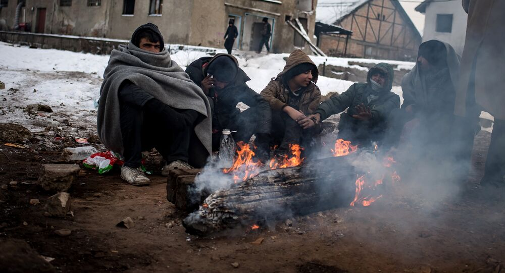 Migrants warm up around a fire at a makeshift shelter at an abandoned warehouse in Belgrade on January 10, 2017, as temperatures dropped to -15 degrees Celsius overnight