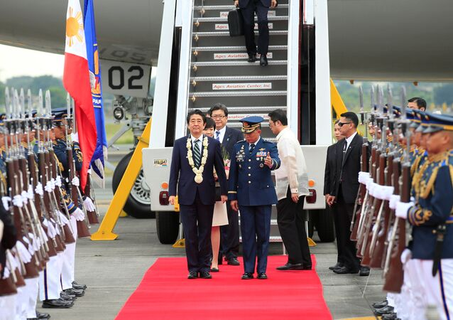 Japanese Prime Minister Shinzo Abe is led the way by a Philippine military official to review honour guards upon arrival for a state visit in metro Manila, Philippines January 12, 2017