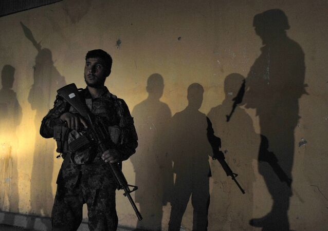 An Afghan security official is surrounded by the shadows of colleagues (File)