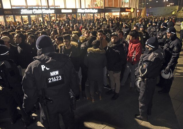 Police officers surround a group of men in front of the Cologne, western Germany, main station, Saturday, Dec. 31, 2016