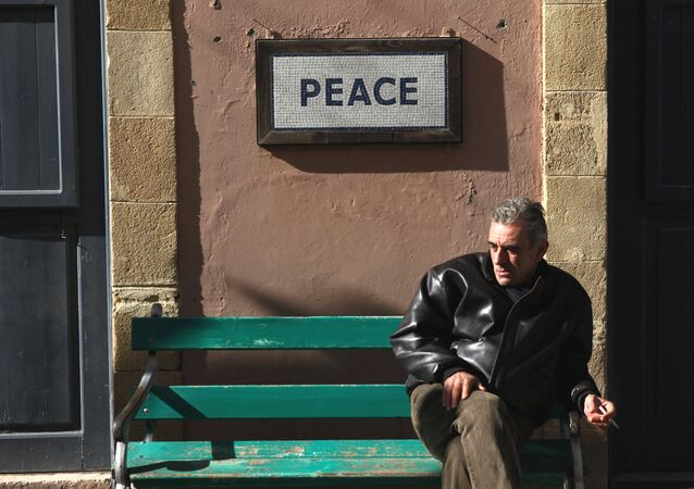 A man sits on a bench under a peace sign near the UN-controlled buffer zone in Nicosia, Cyprus January 9, 2017.