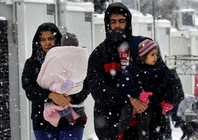 Stranded Syrian refugees carry their children through a snow storm at a refugee camp north of Athens, Greece January 10, 2017.