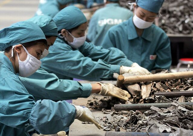 Chinese workers sellect car part scrap to collect aluminum for recycling at a smelting plant (File)
