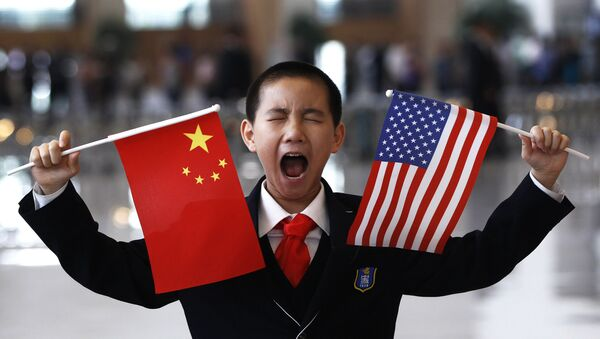 A little boy who is waiting to greet U.S. Secretary of State Hillary Rodham Clinton at the National Museum in Beijing makes a face while holding U.S. and Chinese flags Friday, May 4, 2012 - Sputnik International