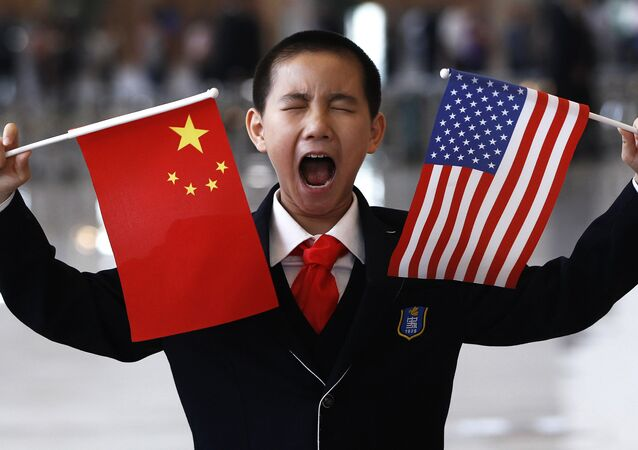 A little boy who is waiting to greet U.S. Secretary of State Hillary Rodham Clinton at the National Museum in Beijing makes a face while holding U.S. and Chinese flags Friday, May 4, 2012