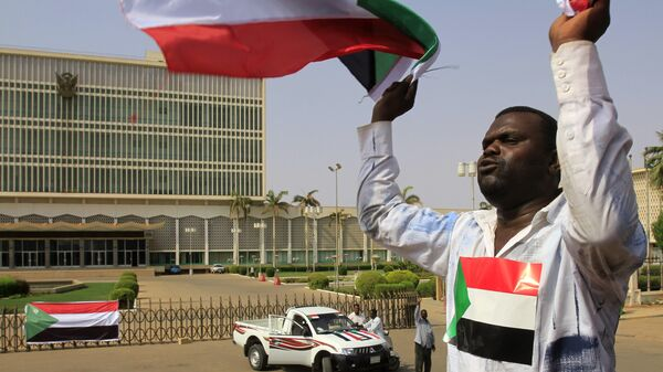 A Sudanese man waves his national flag in Khartoum on July 9, 2011 hours before South Sudan officially declares independence from the north - Sputnik International