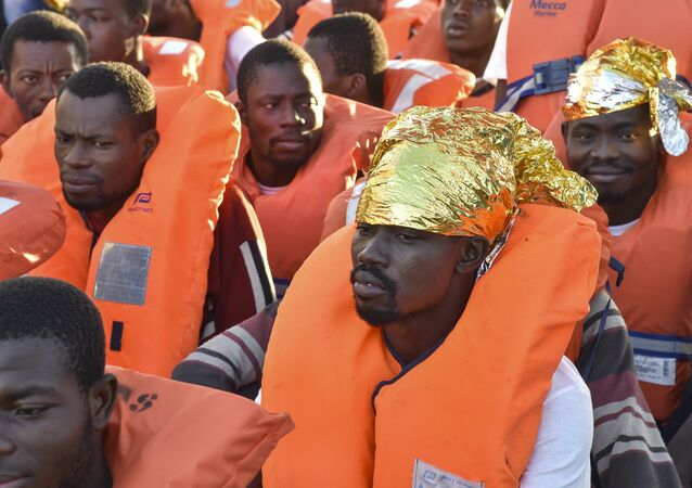 Migrants and refugees wait to be trasferred from the Topaz Responder ship run by Maltese NGO Moas and the Italian Red Cross to the Vos Hestia ship run by NGO Save the Children, on November 4, 2016, a day after a rescue operation off the Libyan coast in the Mediterranean Sea.