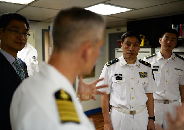 Capt. Kyle P. Higgins, commanding officer of the U.S. 7th Fleet flagship USS Blue Ridge, conducts a ship tour with Vice Adm. Jinlong Shen of the People's Liberation Army Navy.