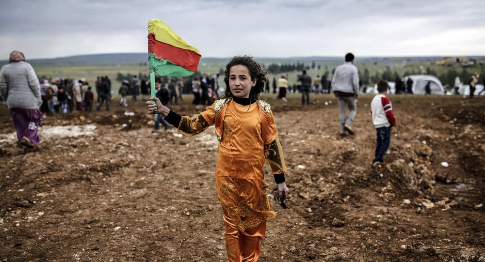 A Syrian Kurdish young woman holds the flag of the Syrian Kurdish Democratic Union Party (PYD) (File)