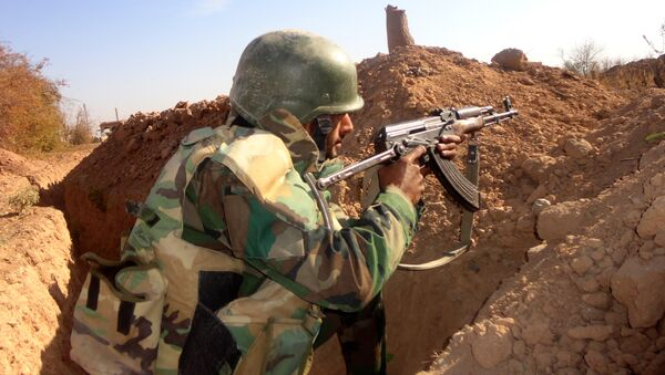 A Syrian army soldier takes aim in the government sector of the town of Houwayqa, which is besieged by Islamic State (IS) group jihadists, in the northeastern Syrian city of Deir Ezzor (File) - Sputnik International