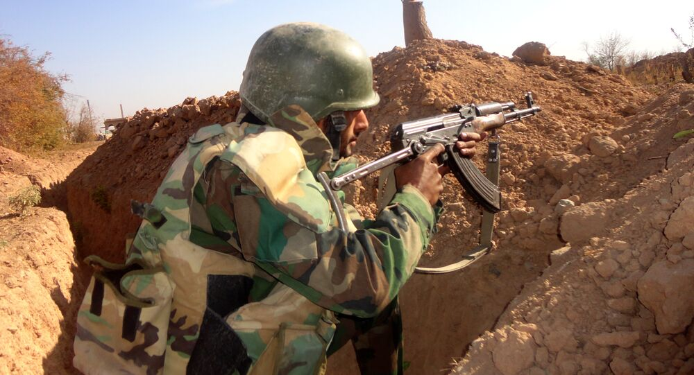 A Syrian army soldier takes aim in the government sector of the town of Houwayqa, which is besieged by Islamic State (IS) group jihadists, in the northeastern Syrian city of Deir ez-Zor (File)