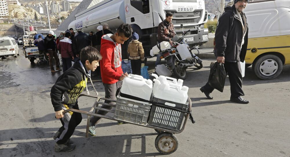 Syrians fill plastic containers with water provided by the Syrian Arab Red Crescent in the capital Damascus on January 10, 2017