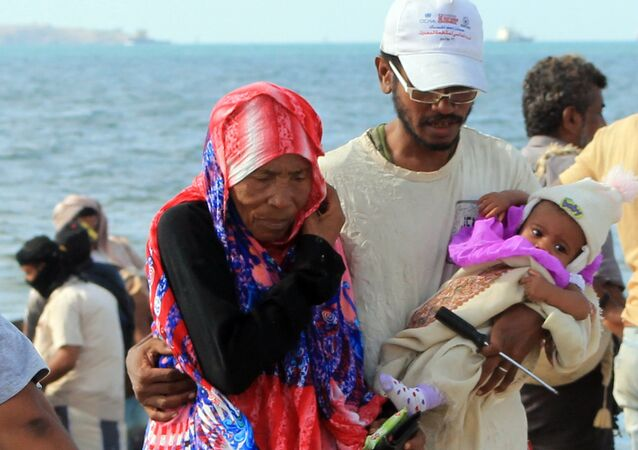 Yemenis walk on a beach of Aden's Tawahi neighbourhood on May 6, 2015 as civilians are trying to escape by sea the ongoing fighting.