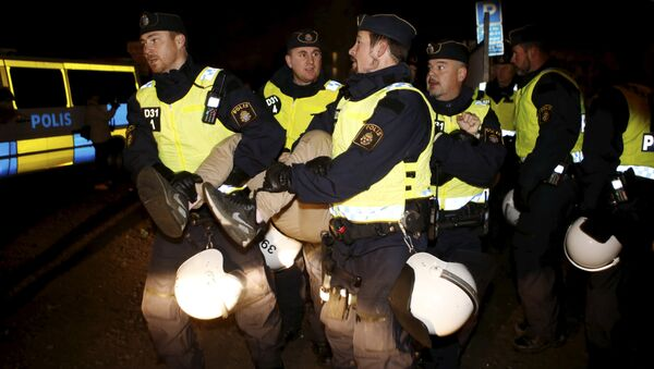 A migrant is carried out by police officers from an illegal camp set up in Malmo - Sputnik International