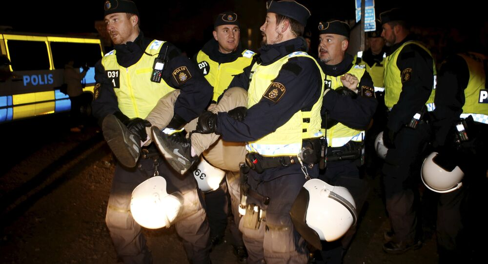 A migrant is carried out by police officers from an illegal camp set up in Malmoe