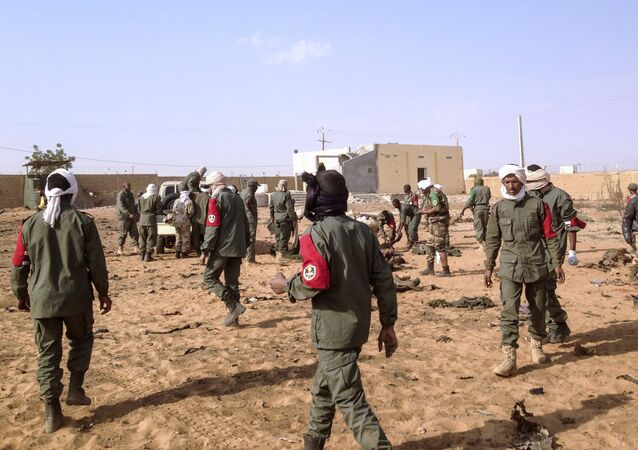 Soldiers attend to wounded and casualties in the aftermath of a suicide bomb attack who ripped through a camp grouping former rebels and pro-government militia in troubled northern Mali left 40 people dead on January 18, 2017 in Gao.