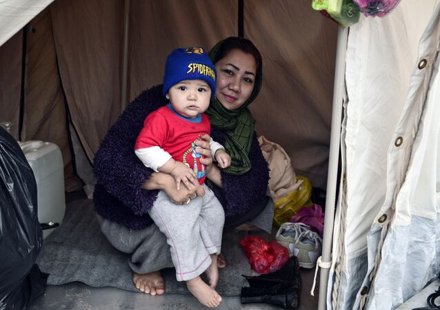 An Afghani refugee woman and mother of three poses with one of her children in their tent set up on a baseball field at a refugee camp in the Hellinikon Olympic Complex, in a southern Athens suburb, on January 11, 2017.