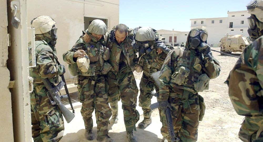 A US Army soldier from 2-8 Infantry, 2nd Brigade, 4th Infantry Division wearing his full chemical protection suit and suffering from heat exhaustion is helped by other soldiers after they sucured an industrial complex which they thought was a possible site for weapons of mass destruction in the central Iraqi town of Baquba 01 May 2003.