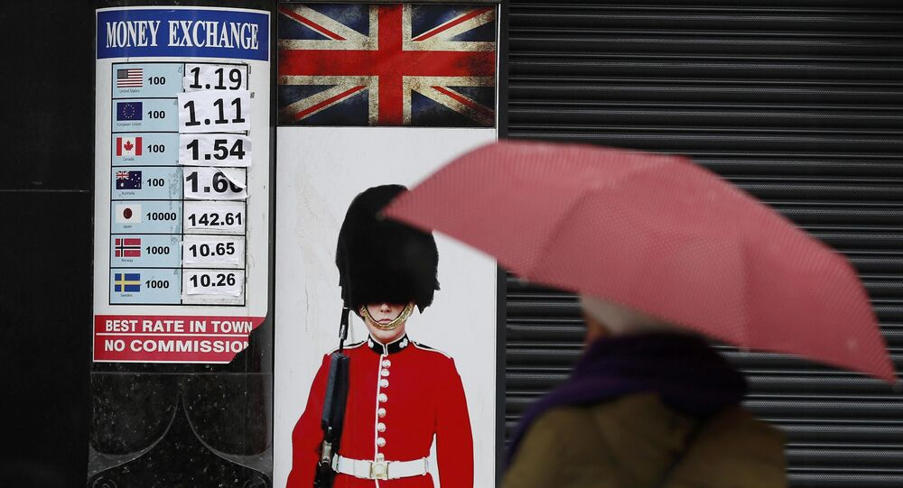 A pedestrian shelters under an umbrella as she walks past a money exchange sign in central London, Britain January 16, 2017.