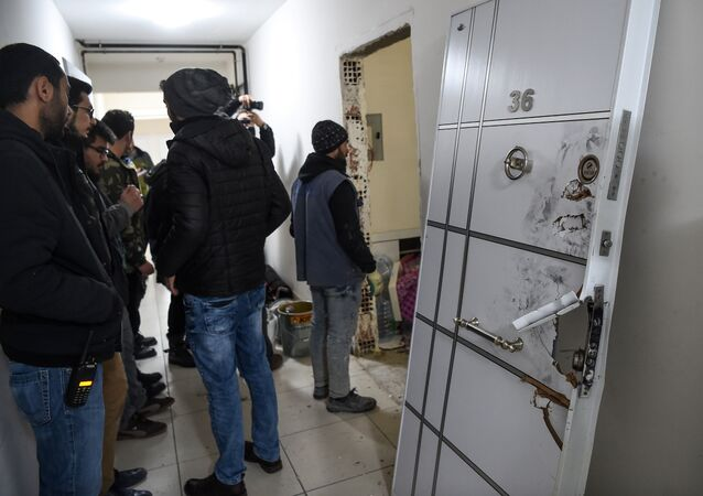 Turkish plain clothes police officers wait next to a damaged door at the apartment where the main suspect in the Reina nightclub rampage was arrested by Turkish police the night before, in Istanbul on January 17, 2017