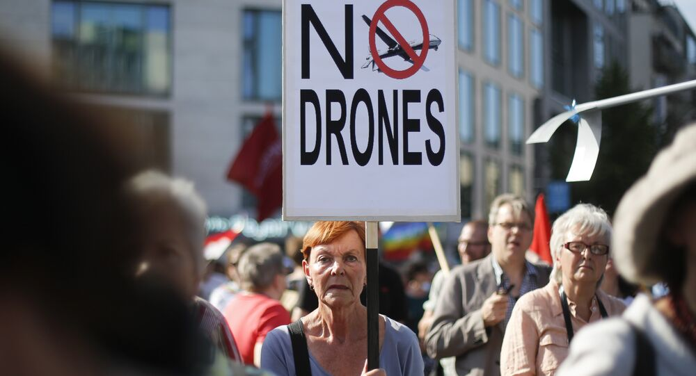 A woman holds a poster against drones during a demonstration against the upcoming visit of United States President Barack Obama in Berlin, Monday, June 17, 2013