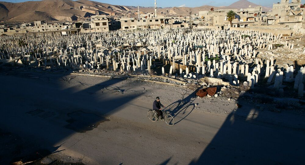 A civilian rides a bicycle past a cemetery in the rebel held besieged Douma neighbourhood of Damascus, Syria January 3, 2017