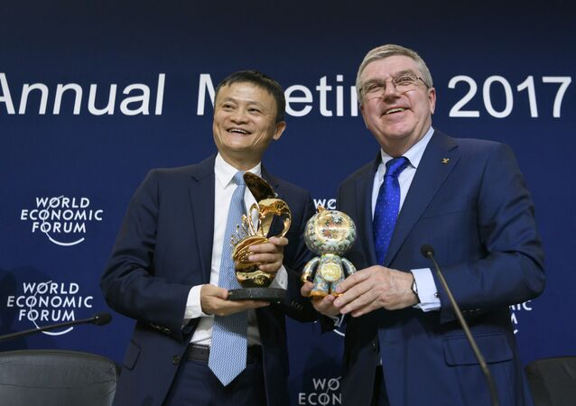 Alibaba Group Founder and Executive Chairman, China's Jack Ma (L) poses next to International Olympic Comittee (IOC) president Thomas Bach as they exchange gifts during the anouncement of a long-term partnership of Alibaba as worldwide sponsor on the sideline of the Forum's annual meeting, on January 19, 2017 in Davos