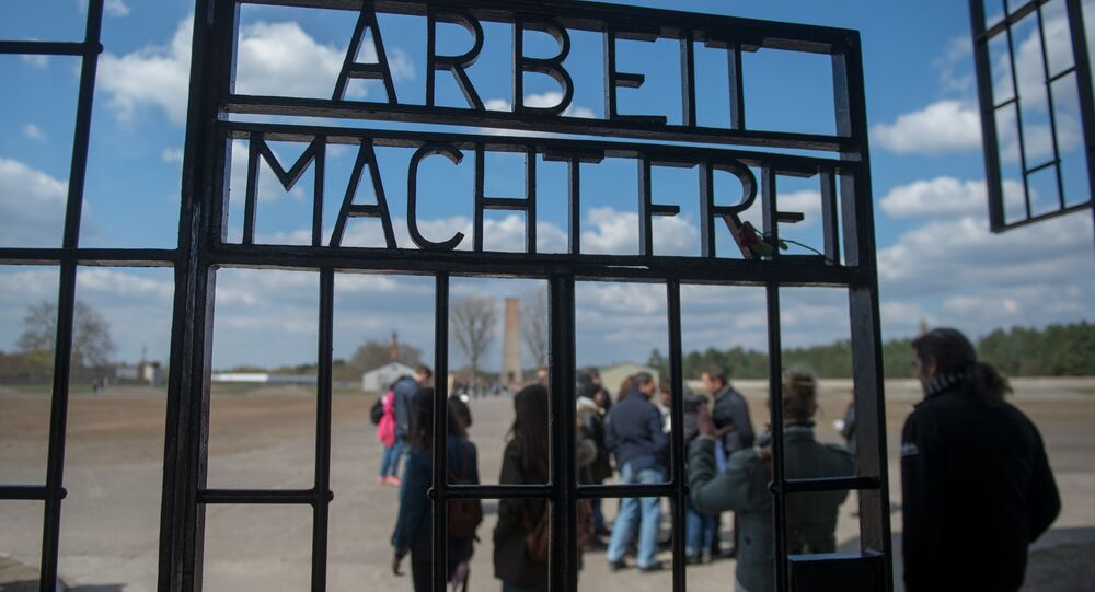 People are seen behind the gate reading Arbeit macht frei (work makes you free) at the entrance to the memorial site of the former Sachsenhausen Nazi concentration camp as they arrive to attend an event to commemorate the 70th anniversary of the camp's liberation, on April 19, 2015 in Oranienburg near Berlin, northeastern Germany.