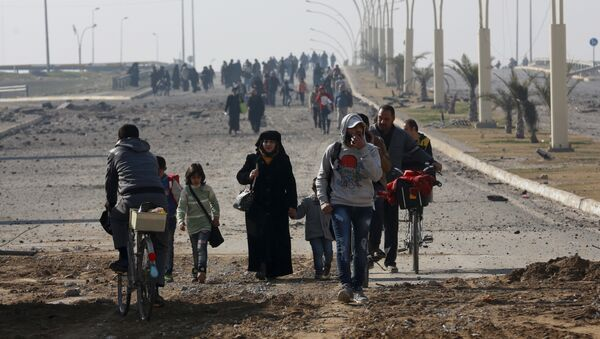 Civilians move away as Iraqi security forces fight against Islamic State militants on the eastern side of Mosul, Iraq, Wednesday, Jan. 18, 2017 - Sputnik International