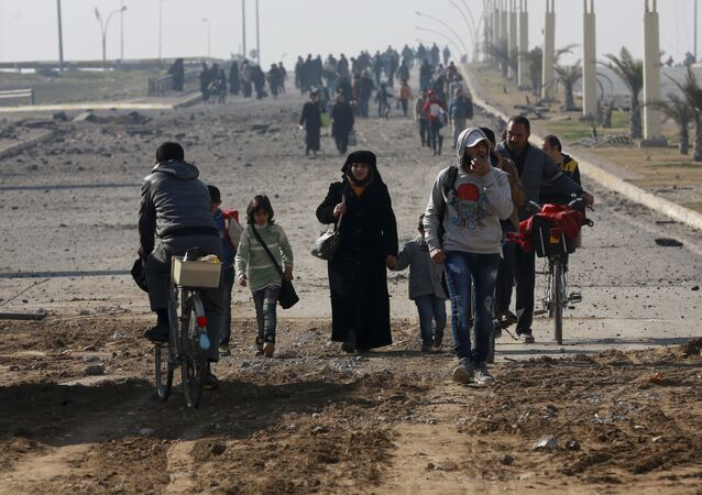 Civilians move away as Iraqi security forces fight against Islamic State militants on the eastern side of Mosul, Iraq, Wednesday, Jan. 18, 2017
