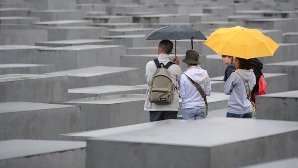 Tourists with umbrellas walk through the Holocaust Memorial on July 28, 2011 in Berlin. - Sputnik International